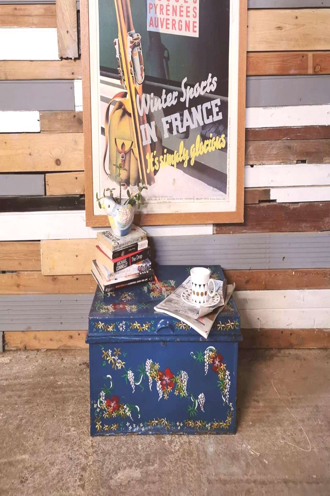 The painted decoration on this metal tin trunk is just so lovely